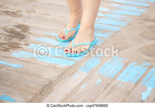 Lady's feet in sandals on beach - csp47949662
