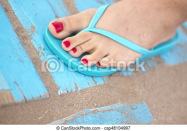 Lady's feet in sandals on beach - csp48104997