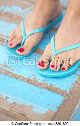 Lady's feet in sandals on beach - csp48391890