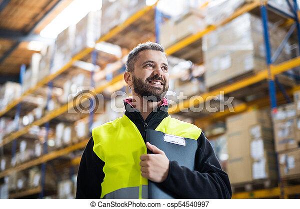 Männliche Lagerarbeiterin mit Klemmbrett. - csp54540997