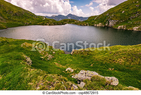 lake in mountains with grass on hillside - csp48672915