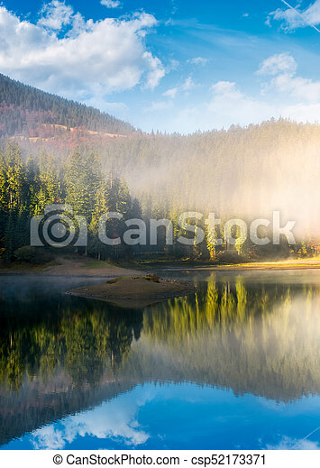lake in spruce forest at foggy sunrise - csp52173371
