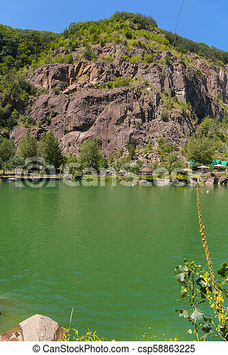 Lake of green water at the foot of the rock with the approach. A place to rest tourists - csp58863225