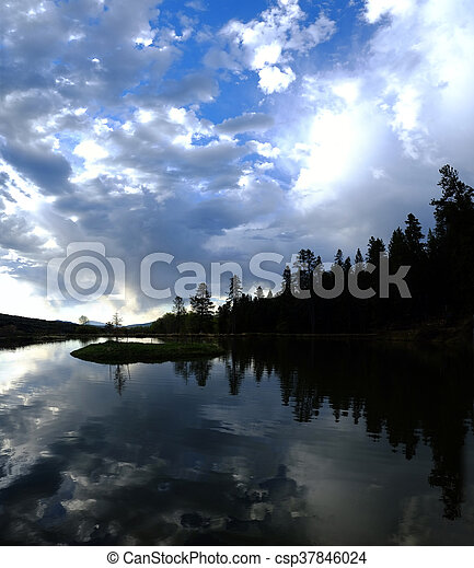 Lake Silhouette Pine Trees Clouds and Water - csp37846024
