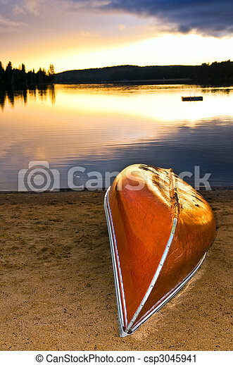 Lake sunset with canoe on beach - csp3045941