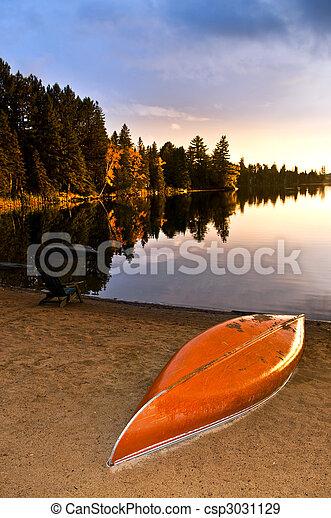 Lake sunset with canoe on beach - csp3031129