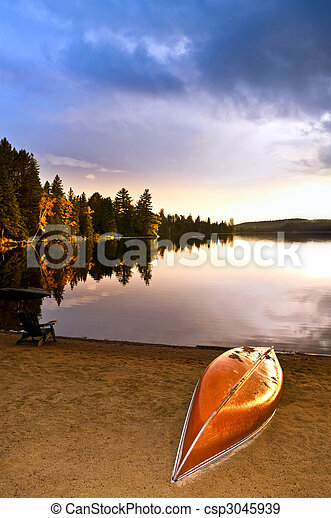 Lake sunset with canoe on beach - csp3045939