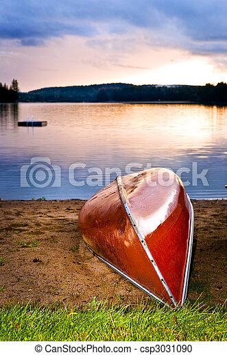 Lake sunset with canoe on beach - csp3031090