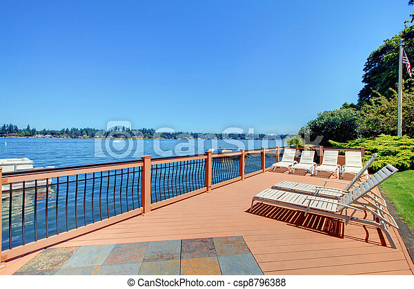 Lake waterfront deck with beach laying down chairs - csp8796388