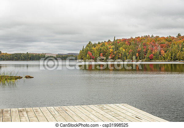 Lake with Fall Colours and Dock in the Foreground - Algonquin Provincial Park, Ontario, Canada - csp31998525