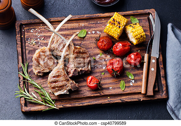 Lamb ribs grilled on cutting board with vegetables - csp40799589