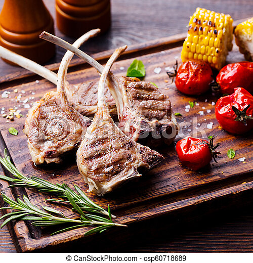 Lamb ribs grilled on cutting board with roasted vegetables. Close up. - csp60718689