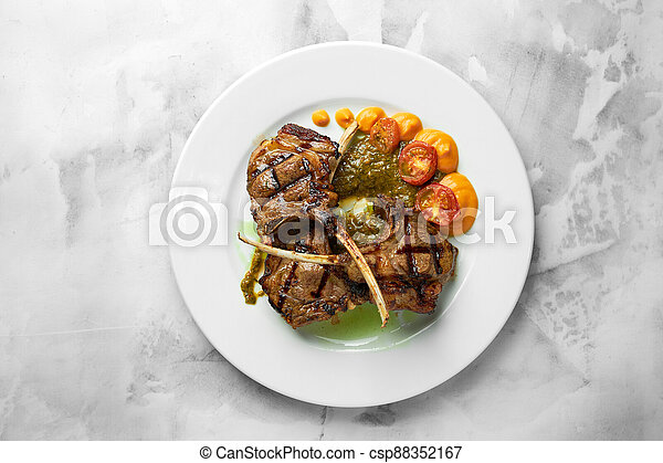 Lamb ribs grilled on cutting board with roasted vegetables. Close up. - csp88352167