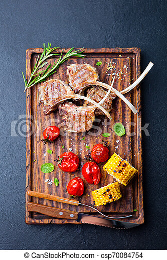 Lamb ribs grilled on cutting board with roasted vegetables. Black background. Top view. - csp70084754