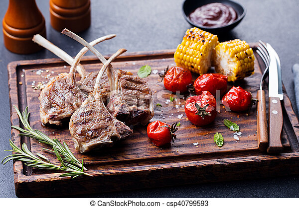 Lamb ribs grilled on cutting board with vegetables - csp40799593