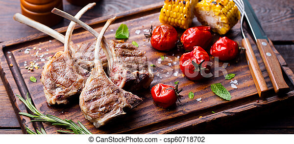 Lamb ribs grilled on cutting board with roasted vegetables. Wooden background. - csp60718702
