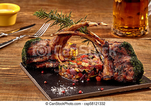 Lamb ribs grilled on cutting board with roasted vegetables and herbs - csp58121332