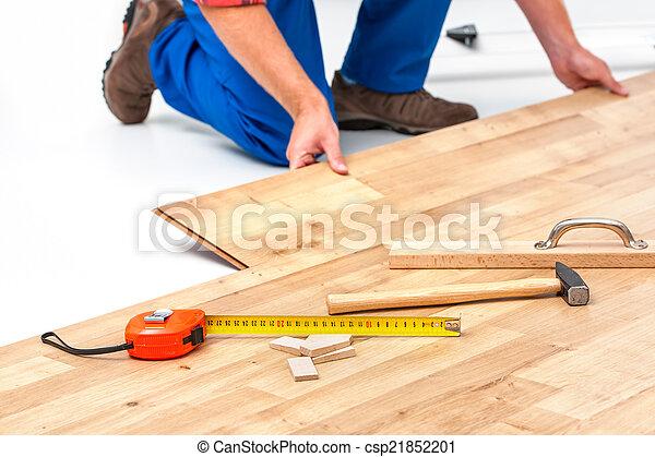 Hombre poniendo suelo laminado - csp21852201