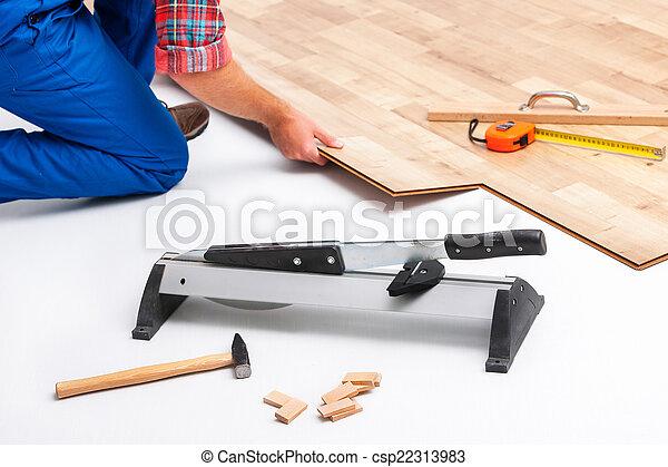 Hombre poniendo suelo laminado - csp22313983