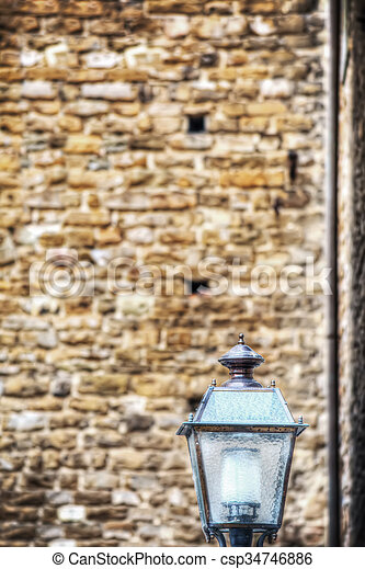 lamppost with a brick wall in the background - csp34746886