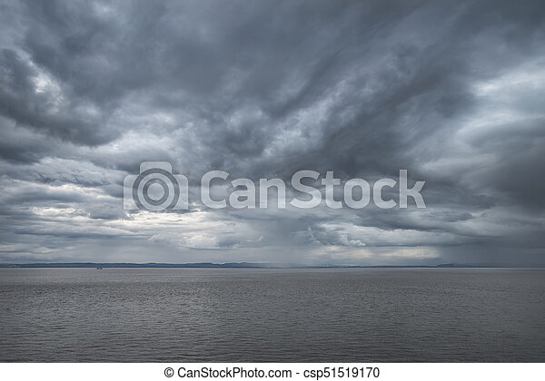 Landscape image of view out to sea with storm cloud sky overhead - csp51519170