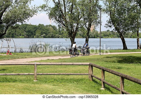 landscape lake with people in bicycle - csp13965028