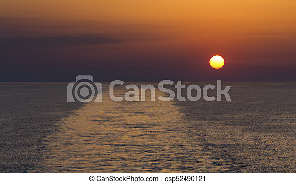 Landscape of a large boat wake on the ocean at sunset - csp52490121