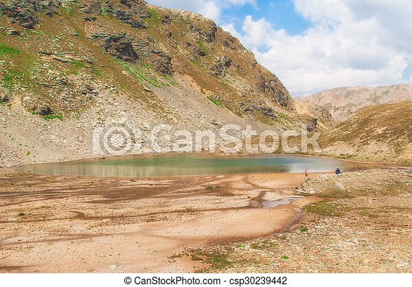 landscape of an alpine lake with cloudy sky - csp30239442