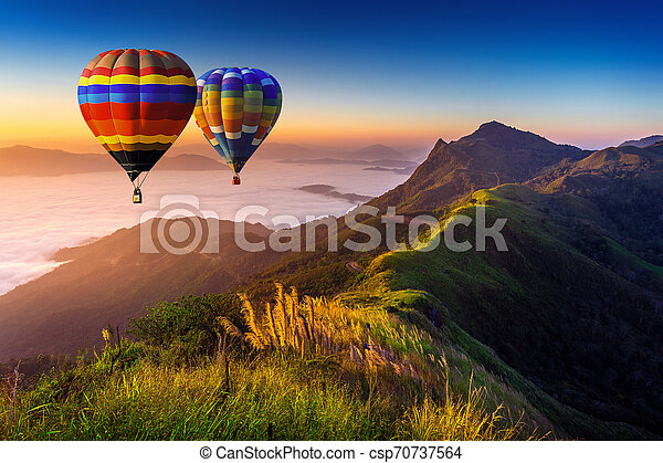 Landscape of morning fog and mountains with hot air balloons at sunrise. - csp70737564