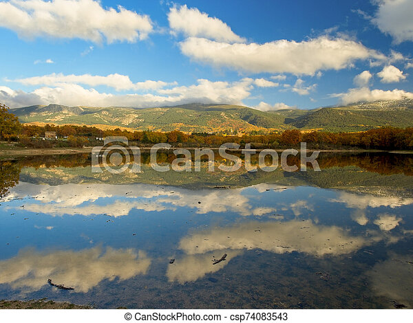 Landscape reflections and clouds in a lake - csp74083543