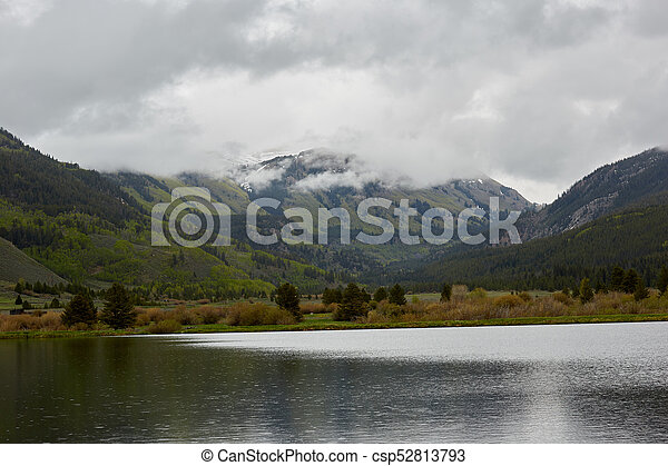 Landscape with lake in cloudy mountains - csp52813793