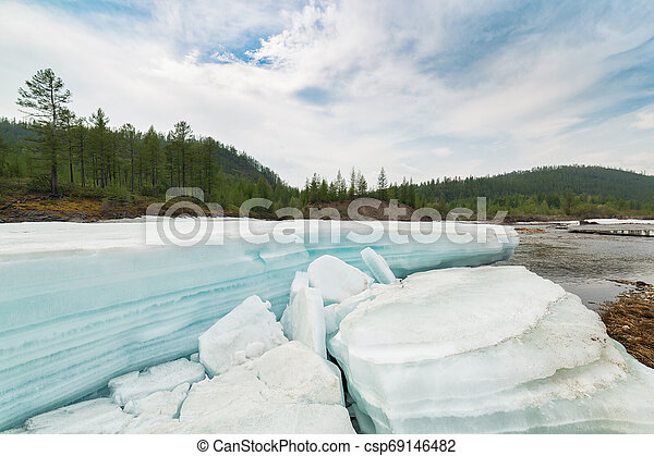 Landscape with turquoise ice on the river - csp69146482