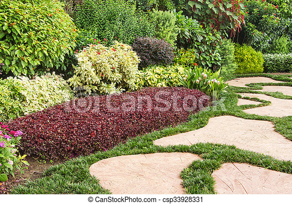 Landscaped garden with flowerbed and colorful plants - csp33928331