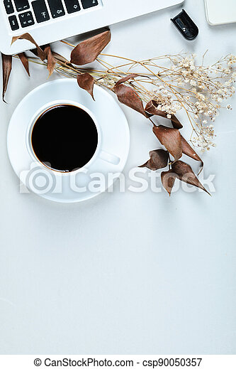 Laptop, mouse and a cup of tea on white desk - csp90050357