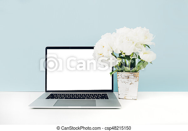 Laptop With White Blank Screen And Flowers In Vase On Table On Blue