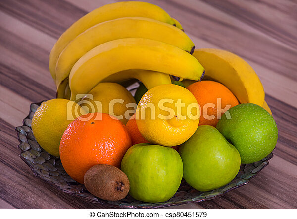 Large bowl with apples, oranges, bananas and other fruits - csp80451579