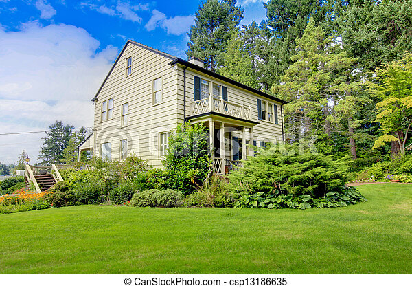 Large brown house exterior with summer garden. - csp13186635