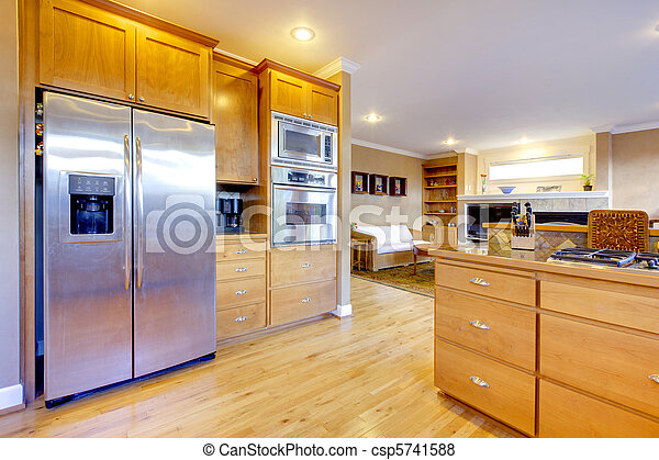 Large kitchen with maple cabinets and large refrigirator. - csp5741588