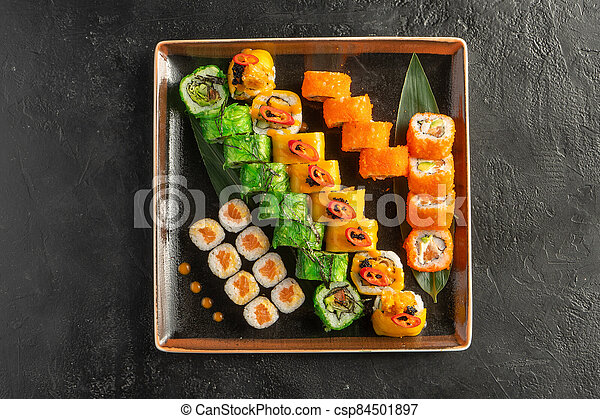 Large maki sushi set with a varied assortment of Japanese rolls in a square plate on a black stone table. - csp84501897