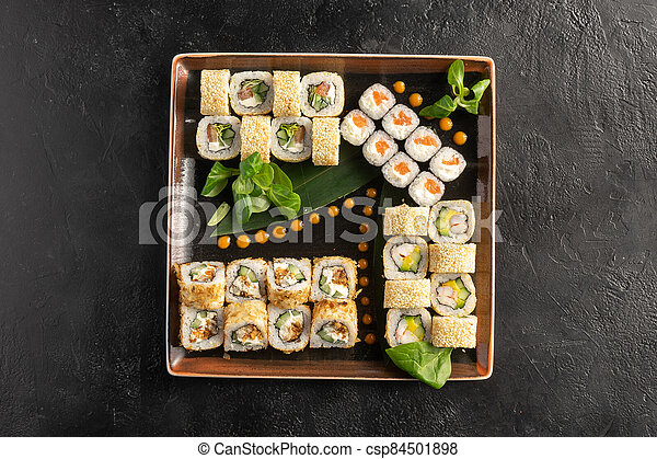 Large maki sushi set with a varied assortment of Japanese rolls in a square plate on a black stone table. - csp84501898