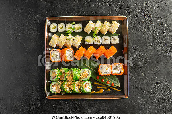 Large maki sushi set with a varied assortment of Japanese rolls in a square plate on a black stone table. - csp84501905