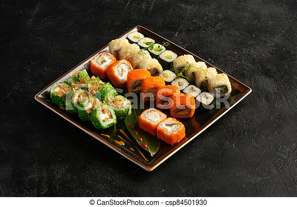 Large maki sushi set with a varied assortment of Japanese rolls in a square plate on a black stone table. - csp84501930