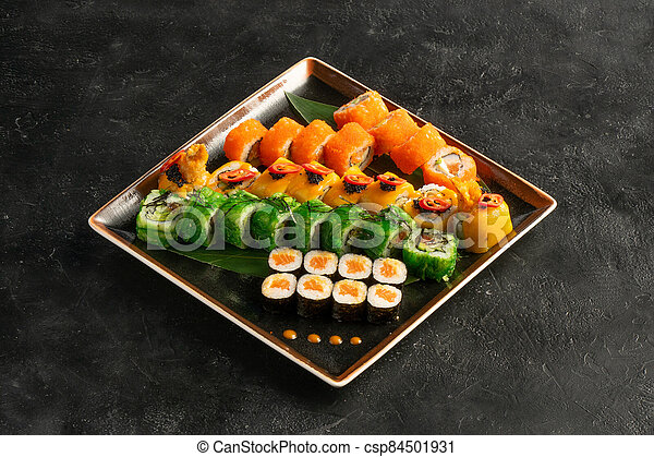 Large maki sushi set with a varied assortment of Japanese rolls in a square plate on a black stone table. - csp84501931