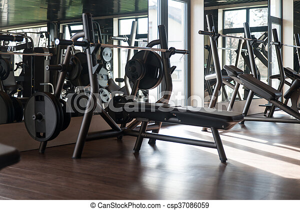 Large modern gym with workout equipment equipment and machines at