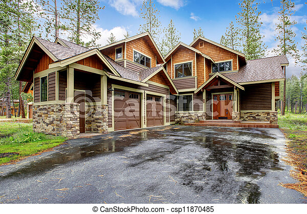 Large mountain cabin house with stone and wet driveway. - csp11870485