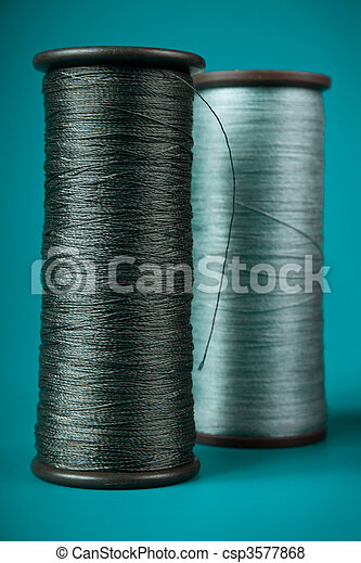 large spools of thread on a blue background - csp3577868