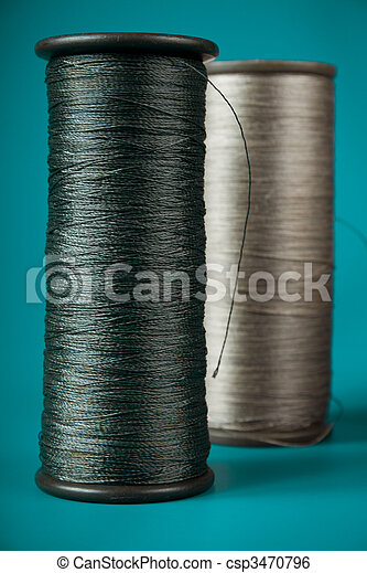 large spools of thread on a blue background - csp3470796