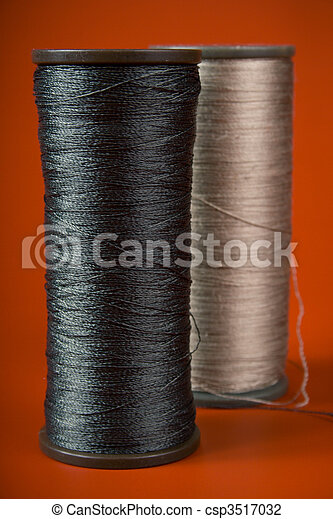 large spools of thread on a red background - csp3517032