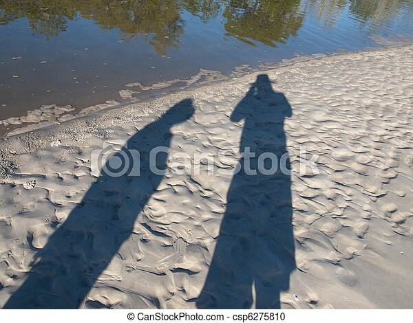 Late afternoon long shadows of male and female tourists exploring a west coast pristine Frazer Island tropical snow white sandy beach- Queensland - Australia. - csp6275810