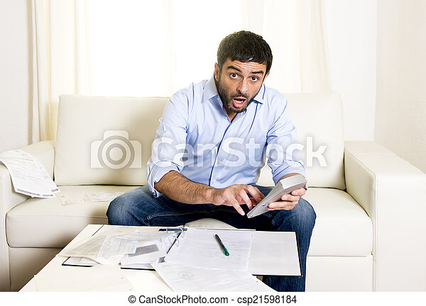 latin business man worried paying bills on couch - csp21598184